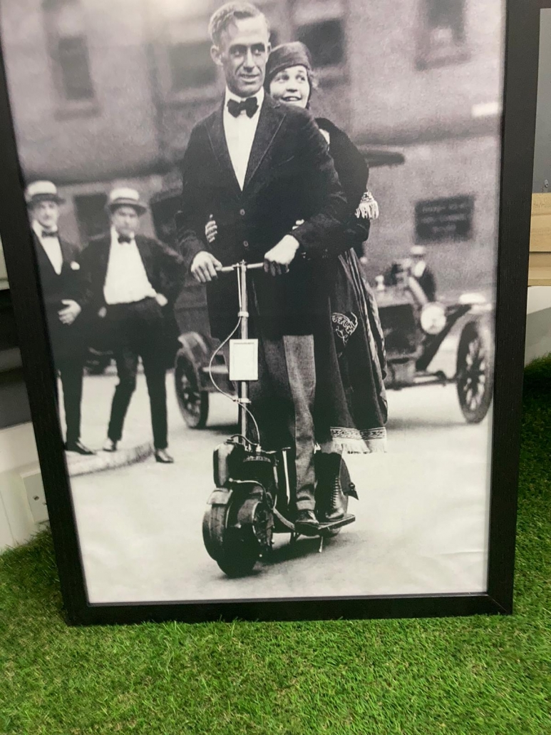 vintage photo of a gentleman riding an electric scooter
